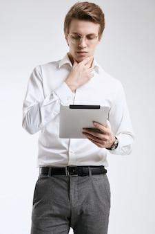 Überzeugter junger geschäftsmann im hemd, das an digitaler tablette arbeitet