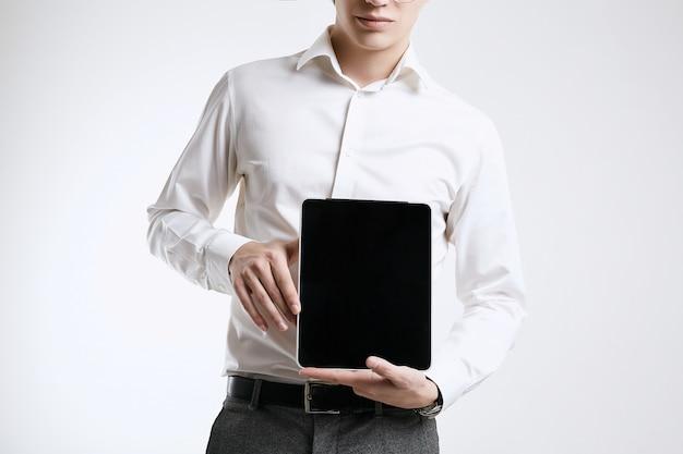 Überzeugter junger geschäftsmann im hemd mit digitaler tablette