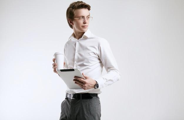 Überzeugter junger geschäftsmann im hemd mit tasse kaffee und tablette