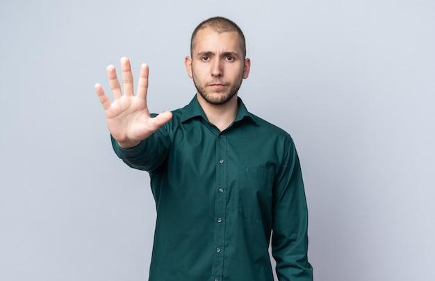 Überzeugter junger gutaussehender kerl, der grünes hemd trägt, das fünf zeigt