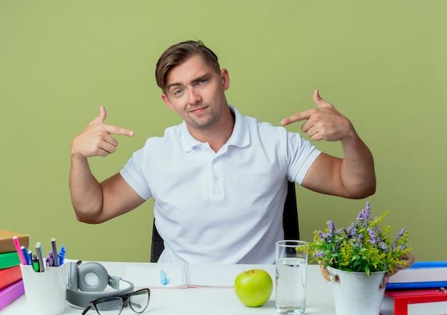 Überzeugter junger hübscher männlicher student, der am schreibtisch sitzt