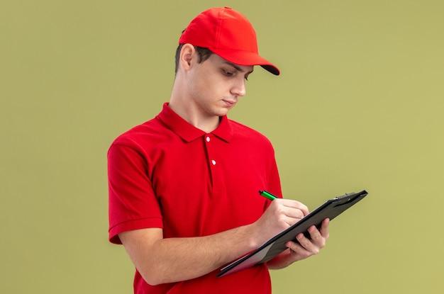 Überzeugter junger kaukasischer lieferbote im roten hemd, das mit stift auf klemmbrett schreibt