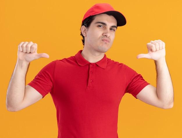 Überzeugter junger kaukasischer lieferbote in blauer uniform und mütze, die auf sich selbst zeigt