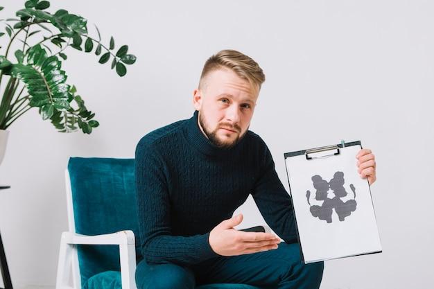 Überzeugter junger männlicher psychologe, der auf dem lehnsessel zeigt rorschach-inkblot testpapier sitzt