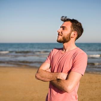 Überzeugter junger mann mit seinen armen kreuzte die stellung am strand