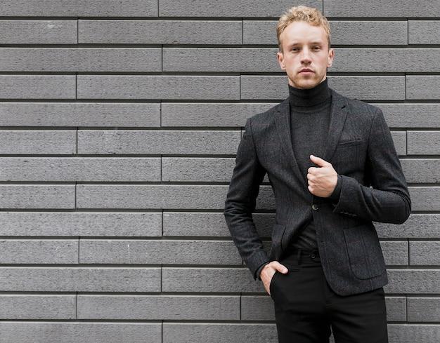Überzeugter junger mann mit seiner hand in der tasche auf grauem hintergrund
