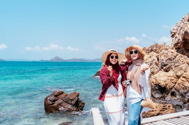 Überzeugter junger moslemischer freund von reisenden auf dem strand. reise-konzept. touristischer freund, der sucht, foto zu machen. zwei schöne asiatische frau.