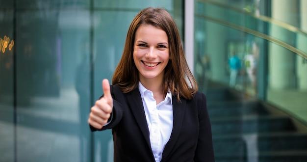 Überzeugter junger weiblicher manager im freien, der daumen aufgibt