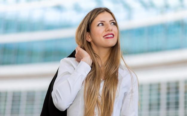 Überzeugter junger weiblicher manager im freien in einer modernen städtischen landschaft