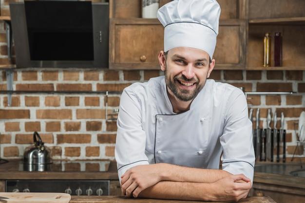 Überzeugter lächelnder chef, der auf küchenarbeitsplatte sich lehnt