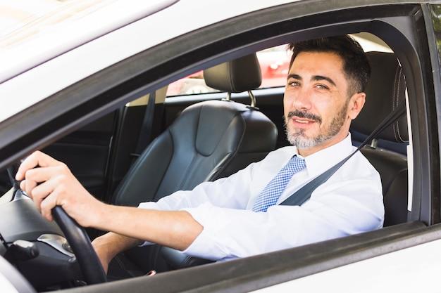 Überzeugter lächelnder geschäftsmann, der kamera beim fahren des autos betrachtet