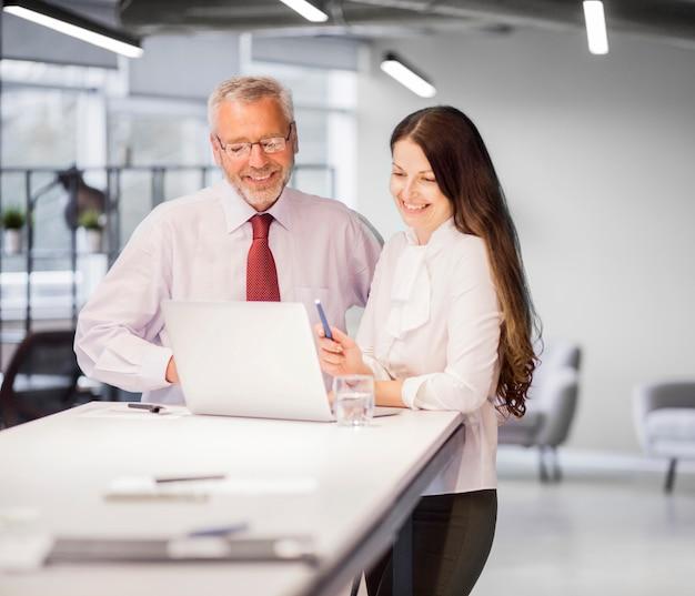 Überzeugter lächelnder geschäftsmann und geschäftsfrau, die laptop im büro betrachtet