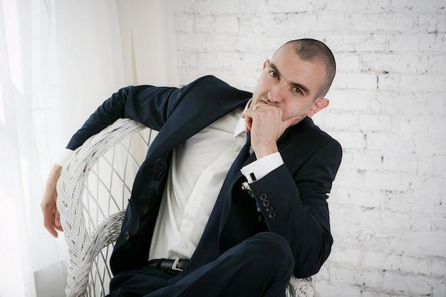 Überzeugter lächelnder junger geschäftsmann, der auf einem weißen stuhl sitzt