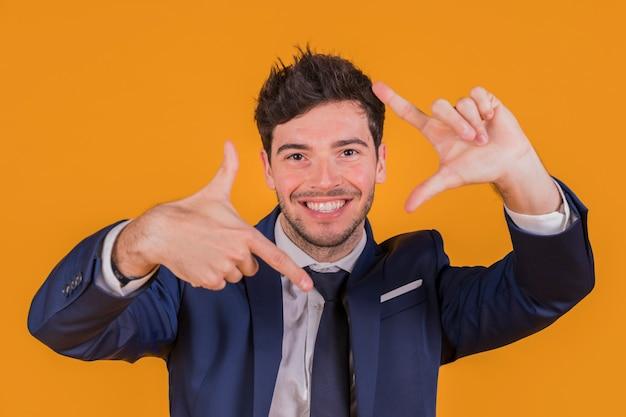 Überzeugter lächelnder junger geschäftsmann, der handrahmen gegen einen orange hintergrund macht