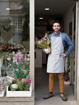 Überzeugter lächelnder junger männlicher florist, der am eingang des blumenladens blumenstrauß in der hand halten steht