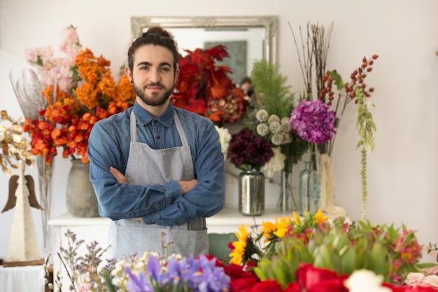 Überzeugter lächelnder junger männlicher florist mit bunten blumen in seinem shop