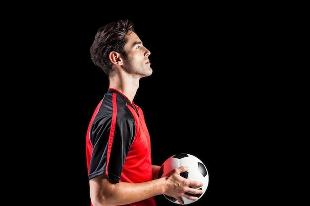 Überzeugter männlicher athlet, der fußball hält