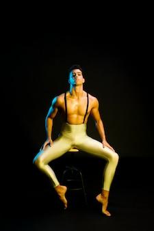 Überzeugter männlicher balletttänzer, der im scheinwerfer sitzt
