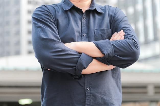 Überzeugter männlicher unternehmensleiter mit den armen kreuzte stellung vor bürogebäude