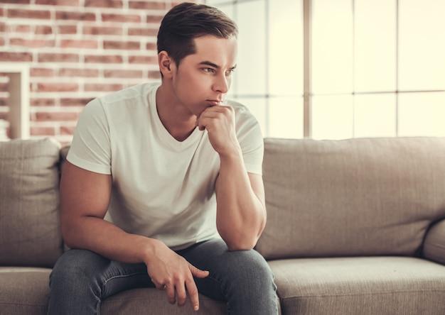 Überzeugter mann, der auf couch sitzt und hand auf kinn hält.