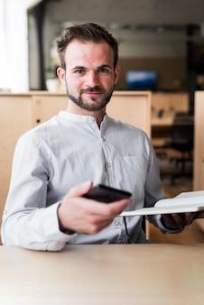 Überzeugter mann, der das mobiltelefon und tagebuch betrachten kamera hält