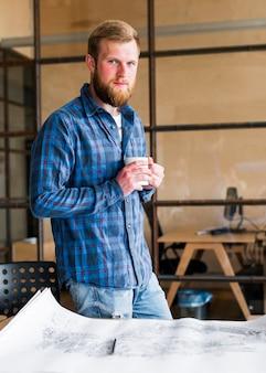 Überzeugter mann, der den tasse kaffee steht nahen schreibtisch hält