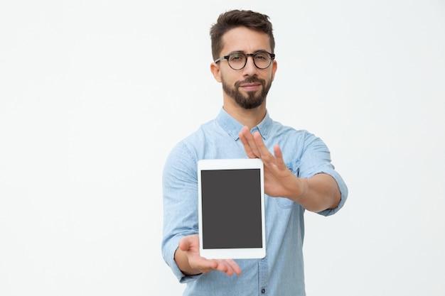 Überzeugter mann, der digitale tablette mit leerem bildschirm zeigt