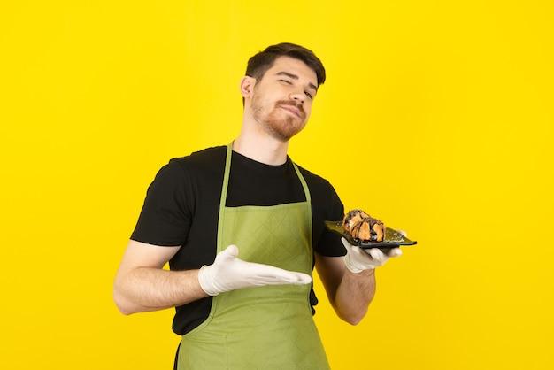 Überzeugter mann, der kuchenscheibe hält und mit der hand auf einem gelb zeigt.