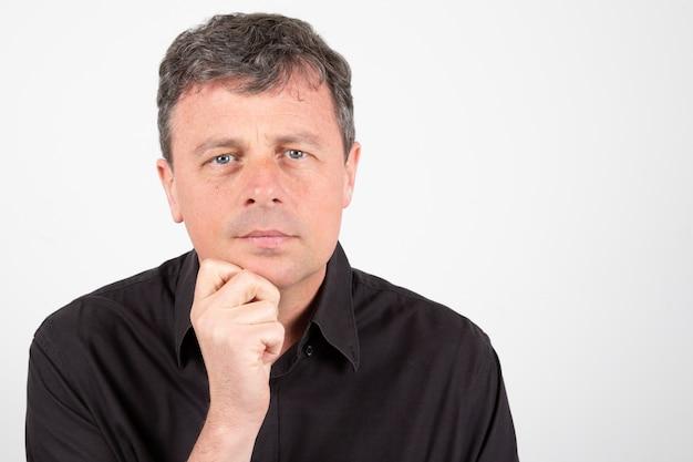 Überzeugter mann von mittlerem alter, der schwarzes hemd der zufälligen kleidung trägt