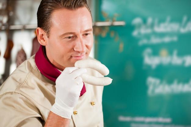Überzeugter metzger, der frische würste in seinem shop riecht