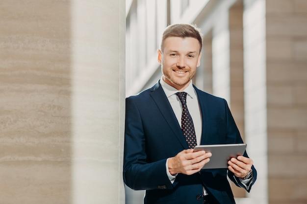 Überzeugter netter männlicher rechtsanwalt liest wirtschaftsnachrichten, hat leichtes lächeln