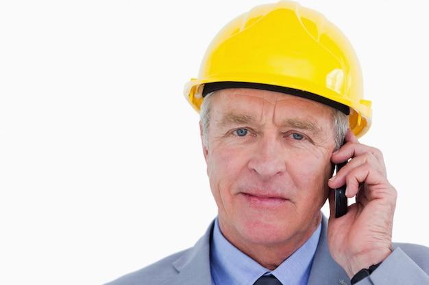 Überzeugter reifer architekt mit sturzhelm am telefon