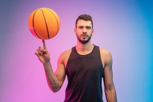 Überzeugter sportler, der basketballball am finger dreht. junger bärtiger europäischer basketballspieler, der kamera betrachtet. getrennt auf blauem und rosa hintergrund. studio-shooting. platz kopieren