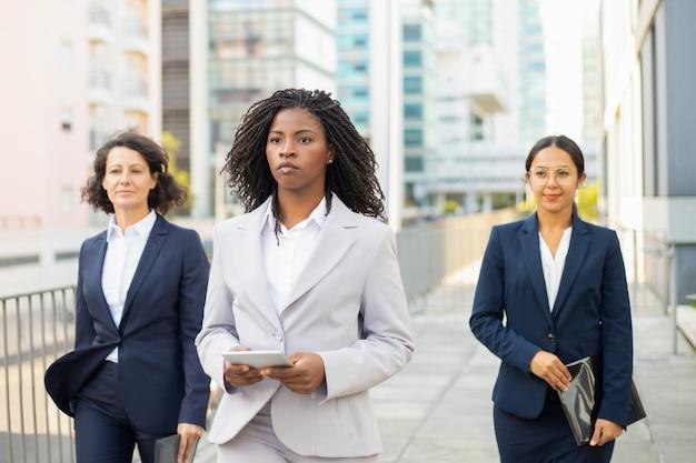 Überzeugter teamleiter, der tablette während des spaziergangs hält. überzeugte geschäftsfrauen, welche die anzüge gehen auf straße tragen. teamwork-konzept