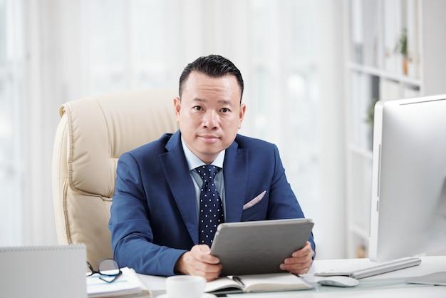 Überzeugter unternehmensberater, der die digitale auflage bereit hält, bei den anfragen zu helfen
