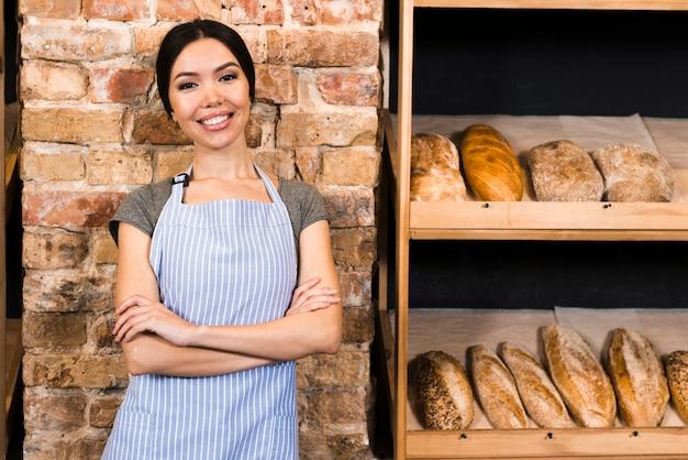 Überzeugter weiblicher bäcker, der nahe dem hölzernen regal mit gebackenen broten steht
