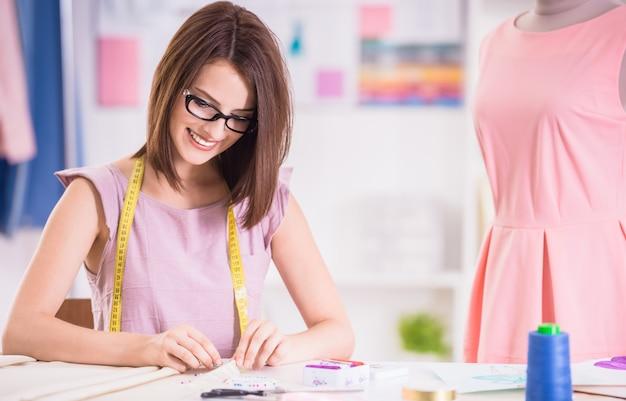 Überzeugter weiblicher designer in den gläsern, die in ihrem studio arbeiten.