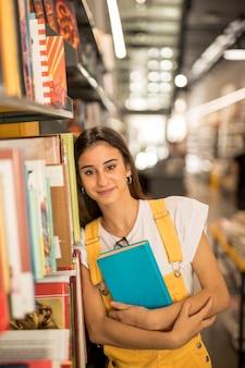 Überzeugtes jugendlich schulmädchen mit bibliotheksbuch