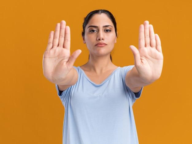 Überzeugtes junges brünettes kaukasisches mädchen, das stoppschild mit zwei händen gestikuliert