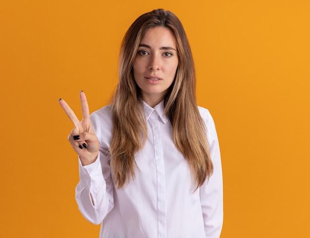 Überzeugtes junges hübsches kaukasisches mädchen gestikuliert sieghandzeichen