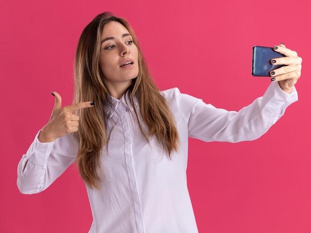 Überzeugtes junges hübsches kaukasisches mädchen schaut und zeigt auf telefon