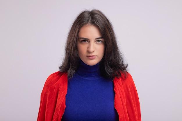 Überzeugtes junges kaukasisches superheldenmädchen im roten umhang