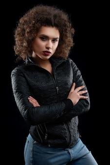Überzeugtes lockiges mädchen, das schwarze jacke und blue jeans trägt.