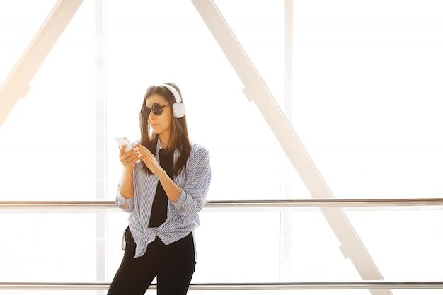 Überzeugtes mädchen oder freiberufler in den kopfhörern hörend musik und betrachten das telefon während im raum, flughafen, büro. handy in den händen von stilvollen modernen jungen frauen mit gläsern.