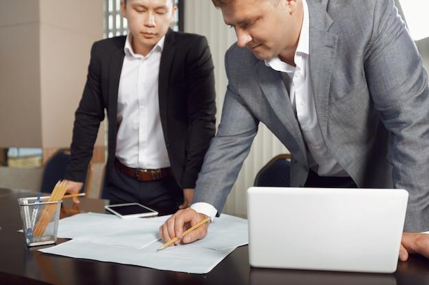 Überzeugtes team von den ingenieuren, die in einem architektenstudio zusammenarbeiten.