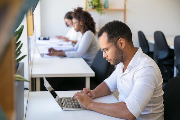 Überzeugtes verschiedenes team, das an projekt im büro arbeitet