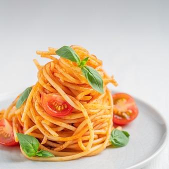 Überzug köstlicher italienischer spaghetti-nudeln in roter tomatensauce mit basilikumblättern
