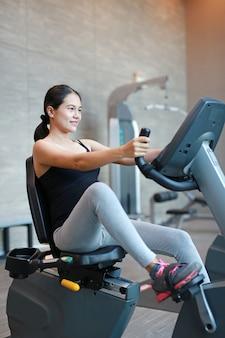 Übung der schwangeren frau auf dem fahrrad in der sporthalle.