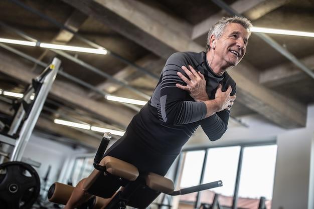 Übung für den unteren rücken von einem älteren mann in einem industriell aussehenden fitnessstudio.