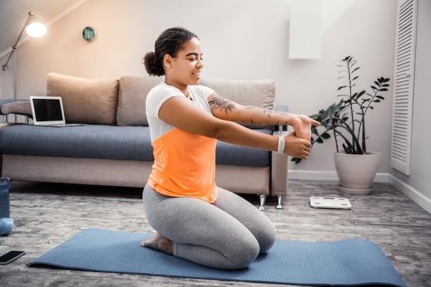 Übung für handflächen. lächelnde attraktive dame, die mit ihrer sportlichen routine glücklich ist, während sie tag zu hause verbringt